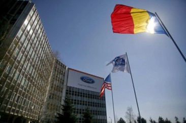 United States, Romania, and Ford Motor Co flags are displayed in front of Ford headquarters in Craiova